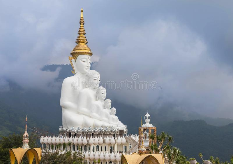 big white buddha statues sitting on valley mountain with fog in Wat Phra That Pha Son Kaew Thailand. stock image