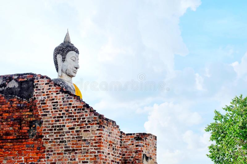 Big white cement buddha statue wearing a yellow coat and big old wall with blue sky, cloud, sunlight and tree at Wat Yai royalty free stock photo