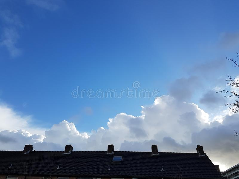 big white clouds above houses in netherlands royalty free stock images