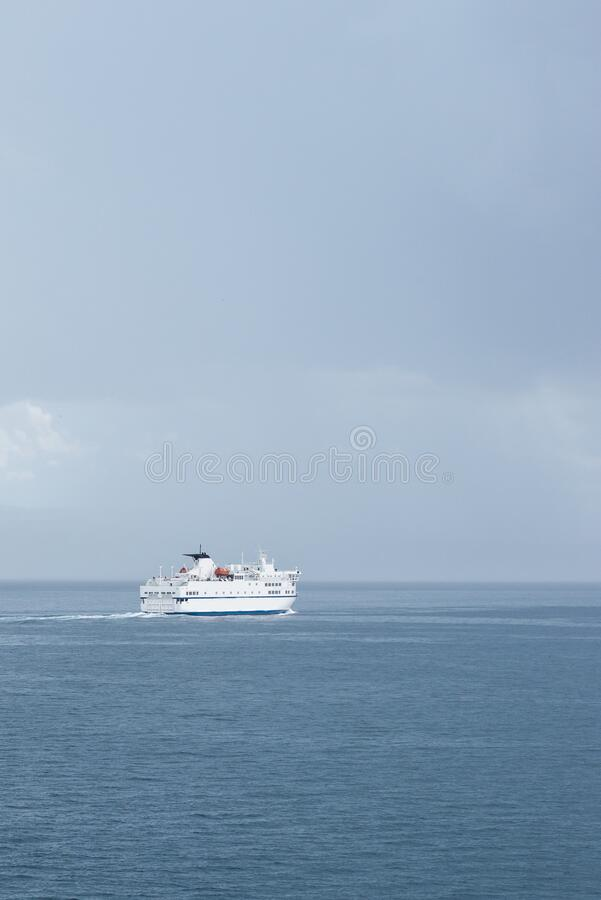 Big white Croatian ferry sailing out of Split going to the islands. Alone on the sea on a rainy storm day, dark clouds stretching. Into the distance royalty free stock photos