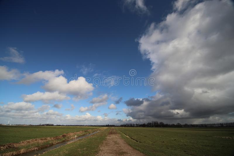 Big white and grey clouds and blue sky in wide angle view over the meadows of the Zuidplaspolder royalty free stock photo