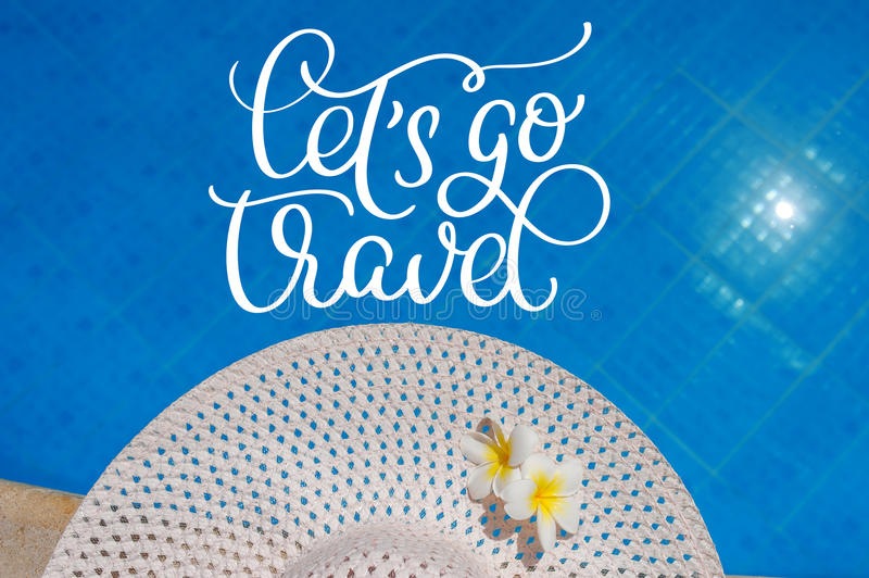 Big white hat on the edge of the pool and text Lets go travel. Calligraphy lettering hand draw stock photo