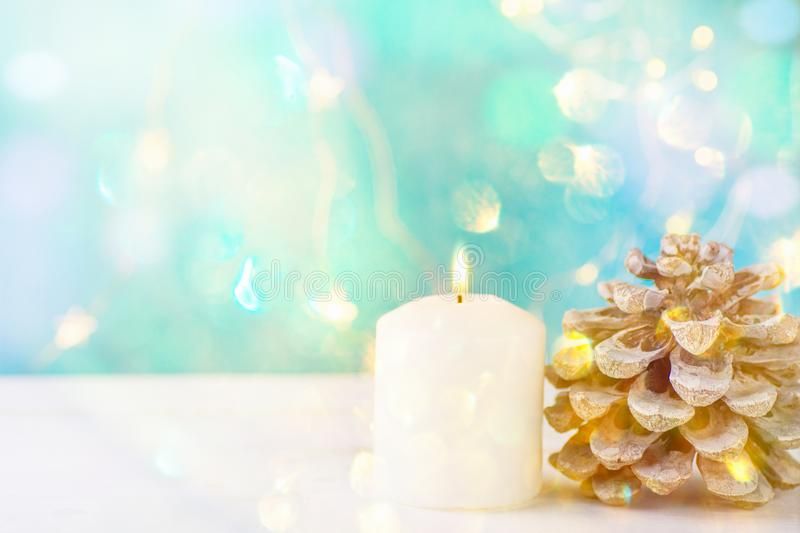 Big White Lit Burning Candle Pine Cone Sparkling Garland Lights Pale Blue Background Christmas New Year Greeting Card. Poster Banner Invitation Template Copy royalty free stock photo
