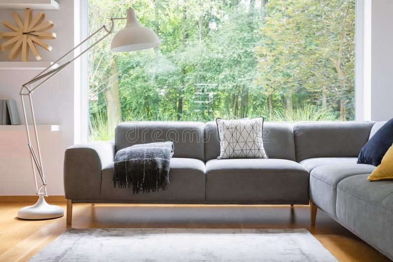 Big white metal lamp standing next to grey corner lounge with blanket and cushion in the real photo bright living room interior wi. Th window stock photo
