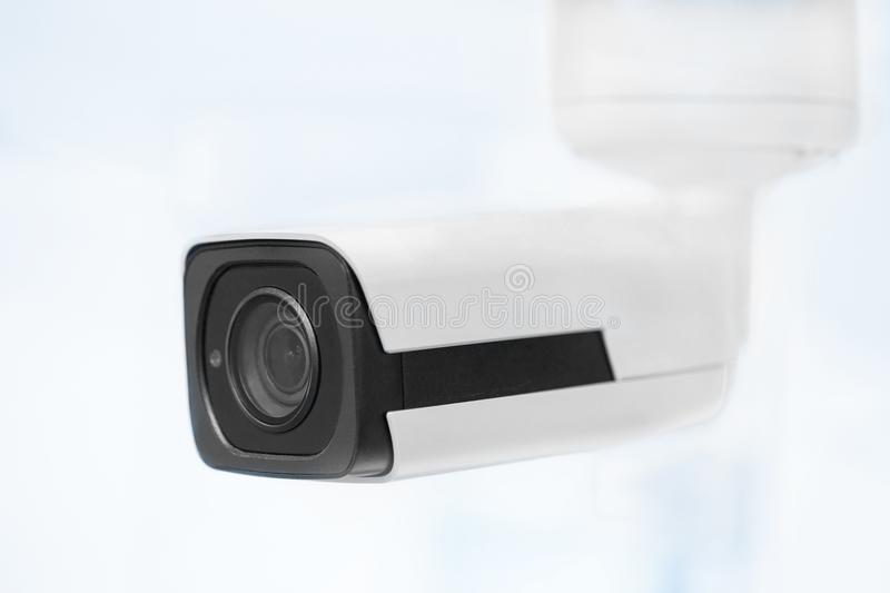 Big white professional surveillance camera. CCTV mounted on ceiling. Security system concept. Copyspace, neutral light blue ba stock images