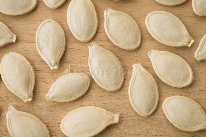 Pumpkin seeds on the wooden board closeup. royalty free stock image