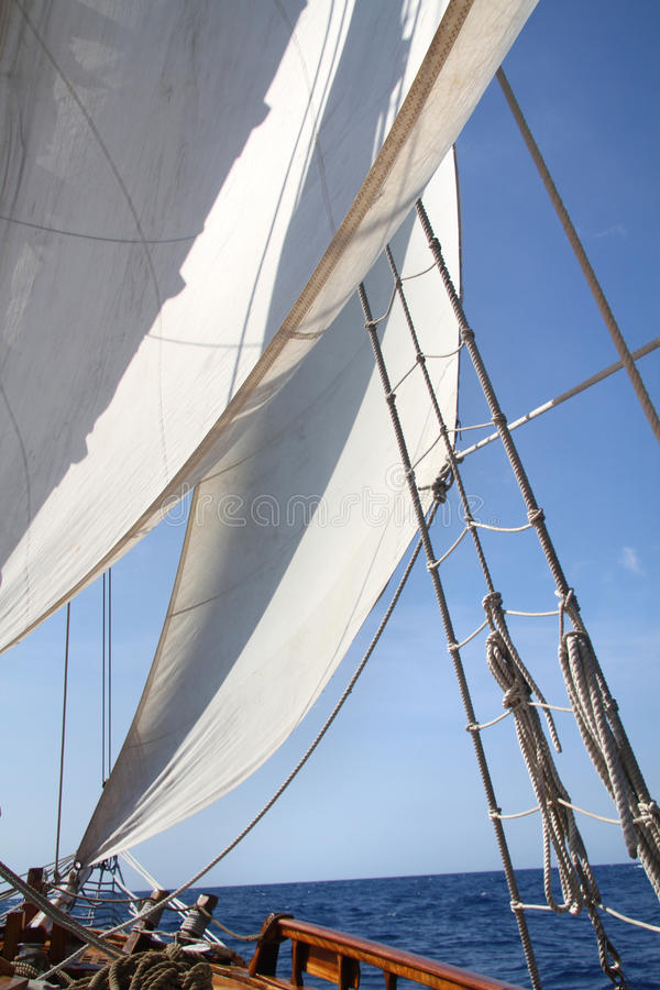 Big white sail. Sailboat in action, big white sail raised over blue clear sky stock photography