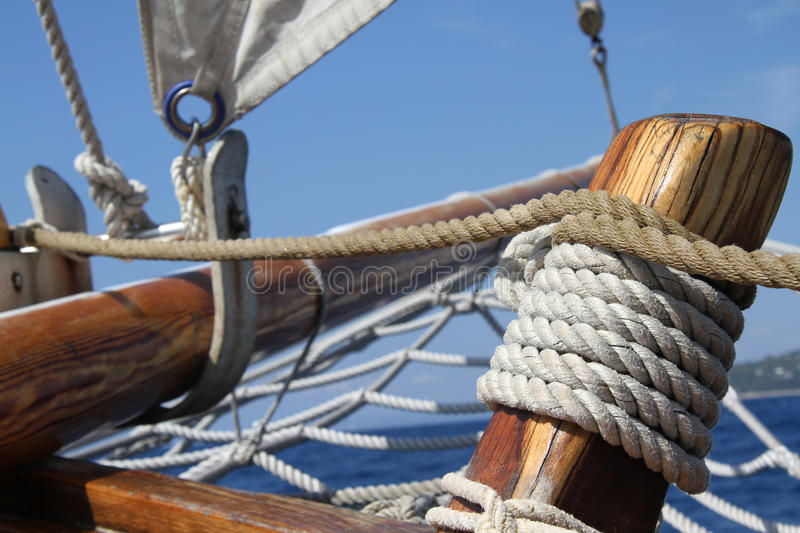 Big white sail. Sailboat in action, big white sail raised over blue clear sky stock photos