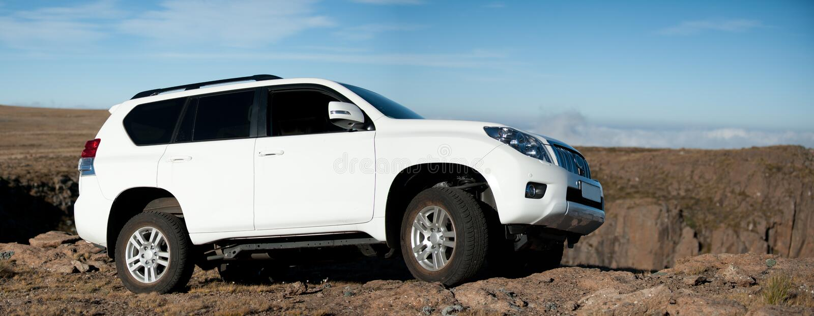 Big white SUV. A panorama of a white SUV 4x4 vehicle in the mountain on the edge of a cliff top royalty free stock images
