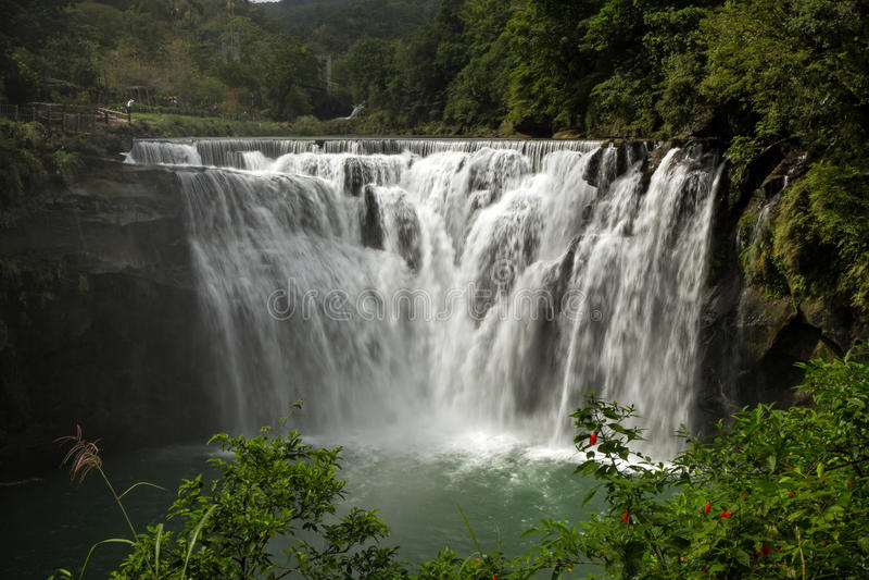 Big and wide Shifen Waterfall in Taiwan. Man standing next to big and wide Shifen Waterfall in Taiwan stock photography