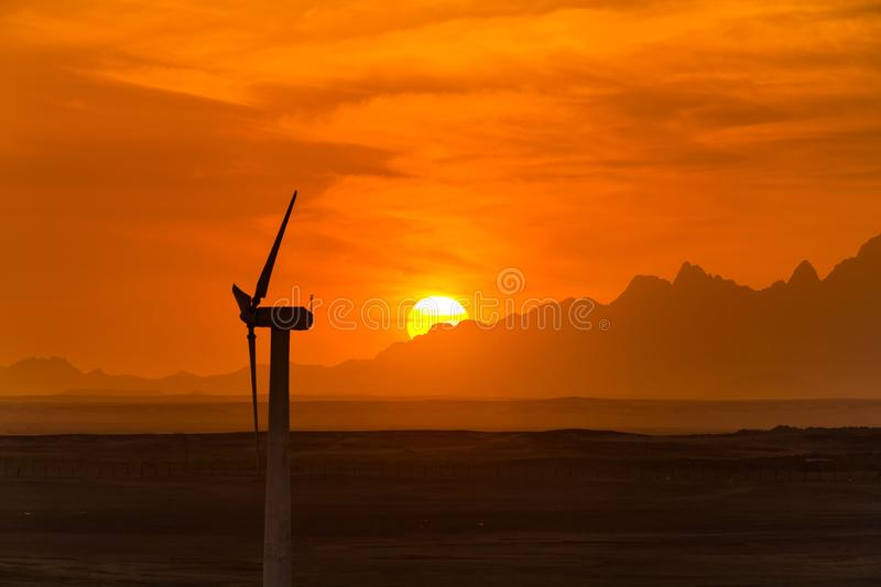 Big wind turbines in the desert against mountains royalty free stock photo