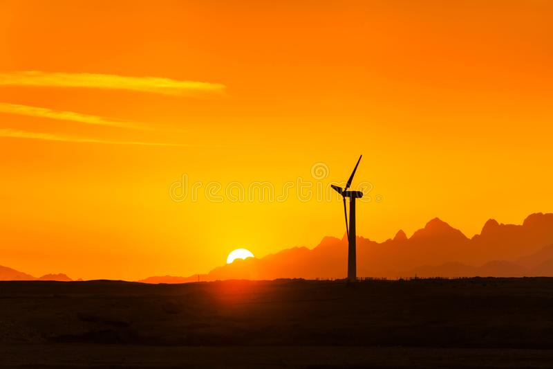 Big wind turbines in the desert against mountains stock photos