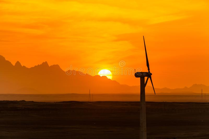 Big wind turbines in the desert against mountains stock images