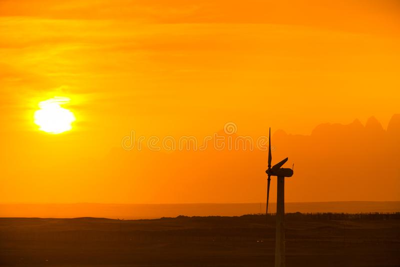 Big wind turbines in the desert against mountains stock photo
