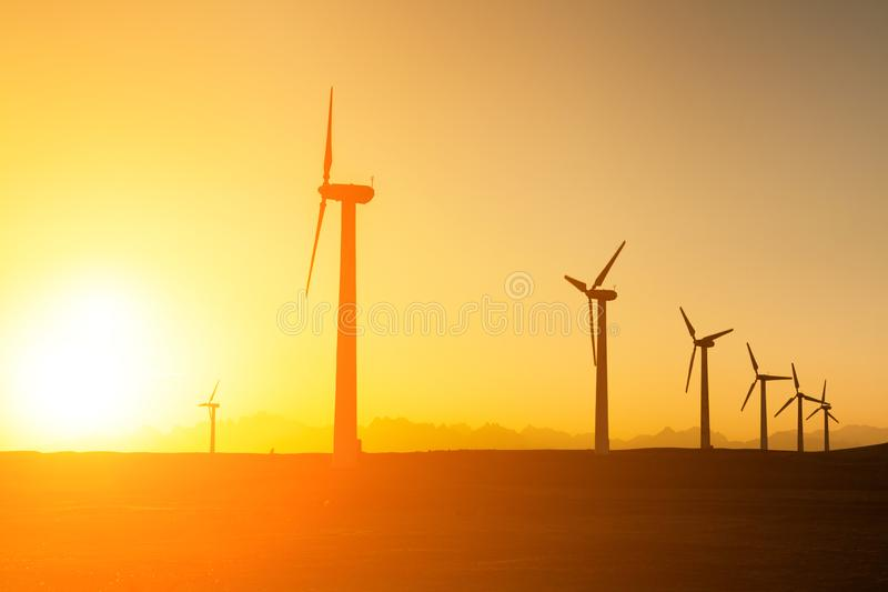 Big wind turbines in the desert at sunset background stock images