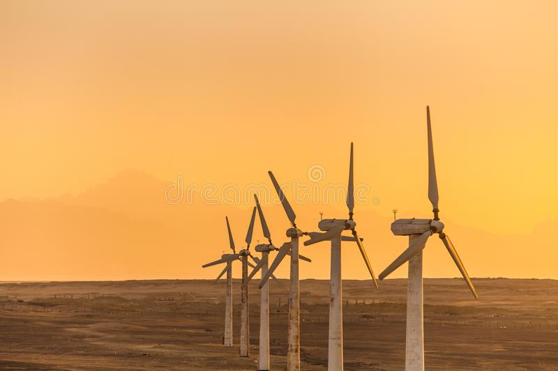Big wind turbines in the desert at sunset background royalty free stock images