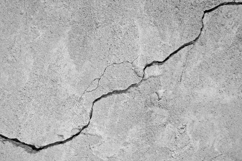 Big winding ascending crack on an gray concrete wall, thin crack diagonally. Copy space royalty free stock photos