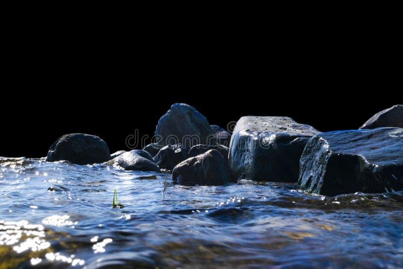 Big windy waves splashing over rocks. Wave splash in the lake isolated on black background. Waves breaking on a stony beach. Big windy waves splashing over rocks stock photos