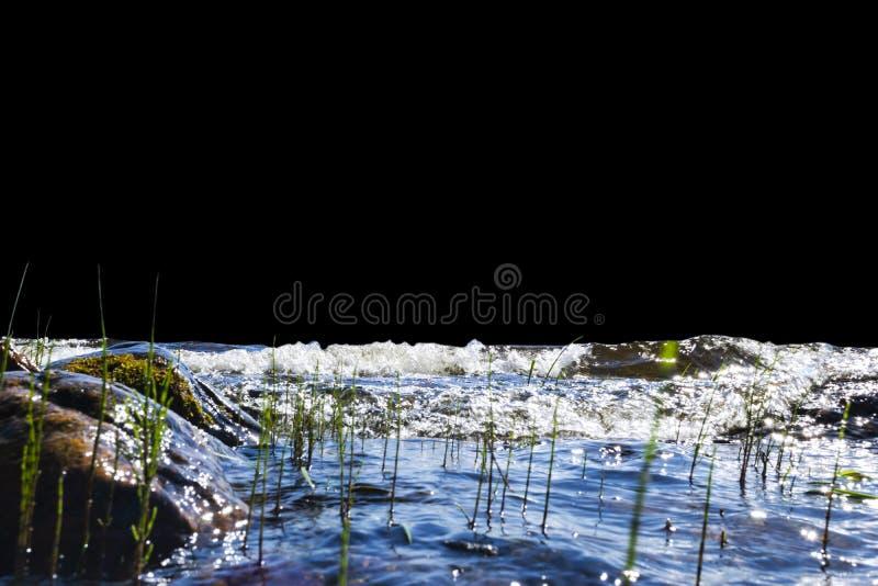 Big windy waves splashing over rocks. Wave splash in the lake isolated on black background. Waves breaking on a stony beach. Big windy waves splashing over rocks royalty free stock images