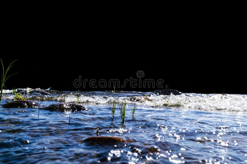 Big windy waves splashing over rocks. Wave splash in the lake isolated on black background. Waves breaking on a stony beach. Forming a spray. Water splashes royalty free stock photos