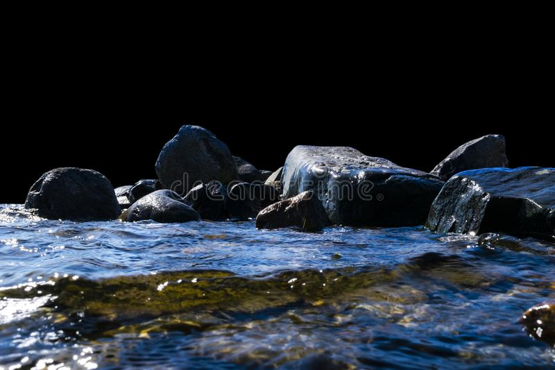 Big windy waves splashing over rocks. Wave splash in the lake isolated on black background. Waves breaking on a stony beach. Forming a spray. Water splashes stock photo