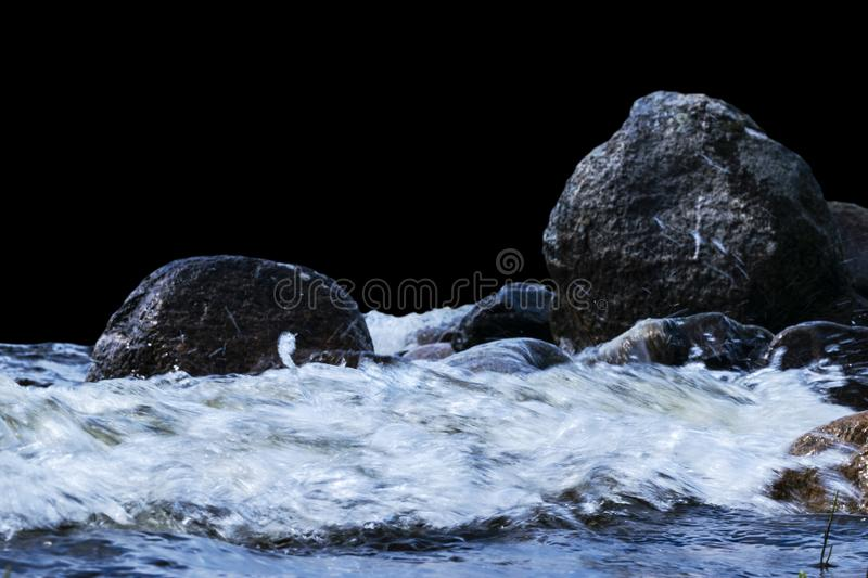 Big windy waves splashing over rocks. Wave splash in the lake isolated on black background. Waves breaking on a stony beach. Forming a spray. Water splashes stock photos