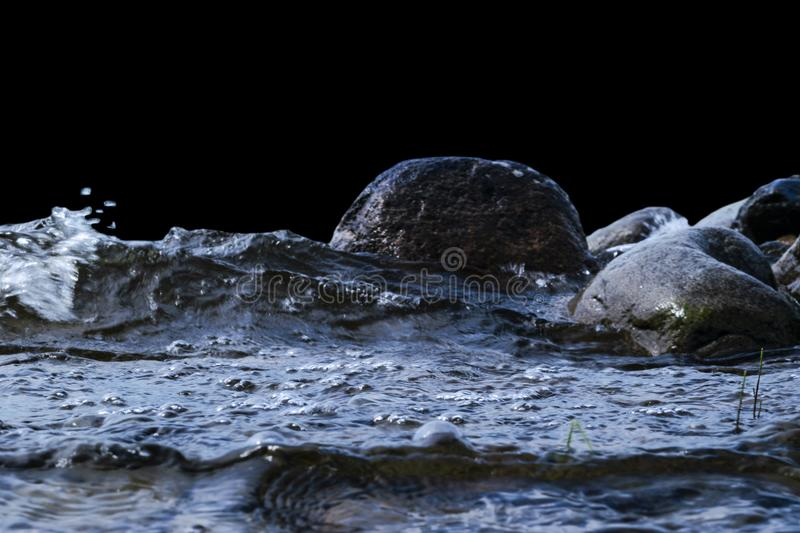 Big windy waves splashing over rocks. Wave splash in the lake isolated on black background. Waves breaking on a stony beach. Forming a spray. Water splashes royalty free stock photo