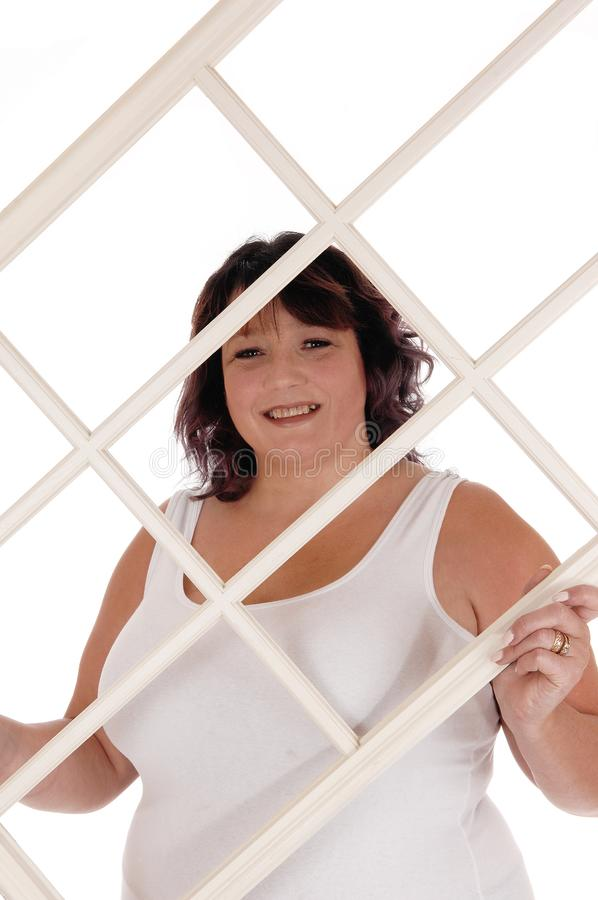 Big woman holding window frame. An oversized woman in her forties standing in a white t-shirt holding up an window frame, isolated for white background stock images