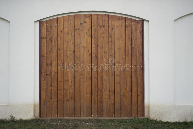 Big wooden barn gate. Monumental farm door, two timber leaf, closed brown gateway with planks and nails stock photos
