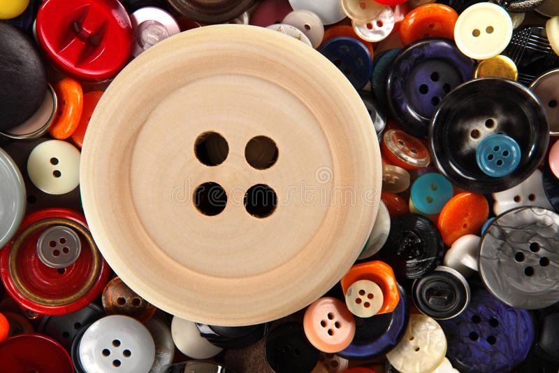 Big wooden button on sewing buttons background royalty free stock image