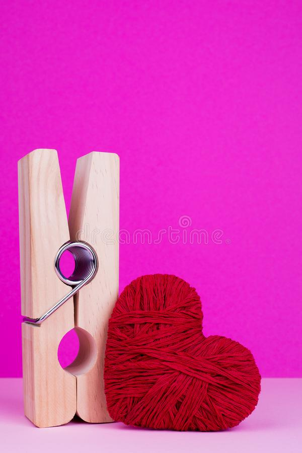 Big wooden clothespin and red heart. Toy heart and clothespin on pink background. St. Valentine`s Day stock photo
