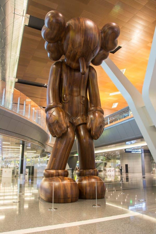 Big wooden girl installation in Haman airport Doha, Qatar. Doha, Qatar - March 10, 2019: Big wooden girl installation in Haman airport Doha, Qatar stock photo