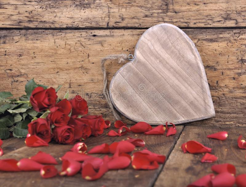 Wooden heart and red roses. Big wooden heart on a plank with red roses and petals royalty free stock photos