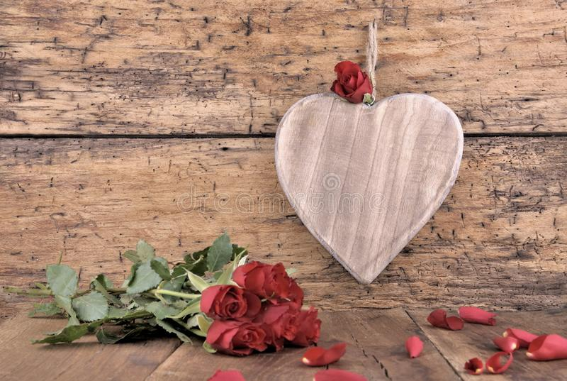 Wooden heart and red roses. Big wooden heart on a plank with red roses and petals royalty free stock photography