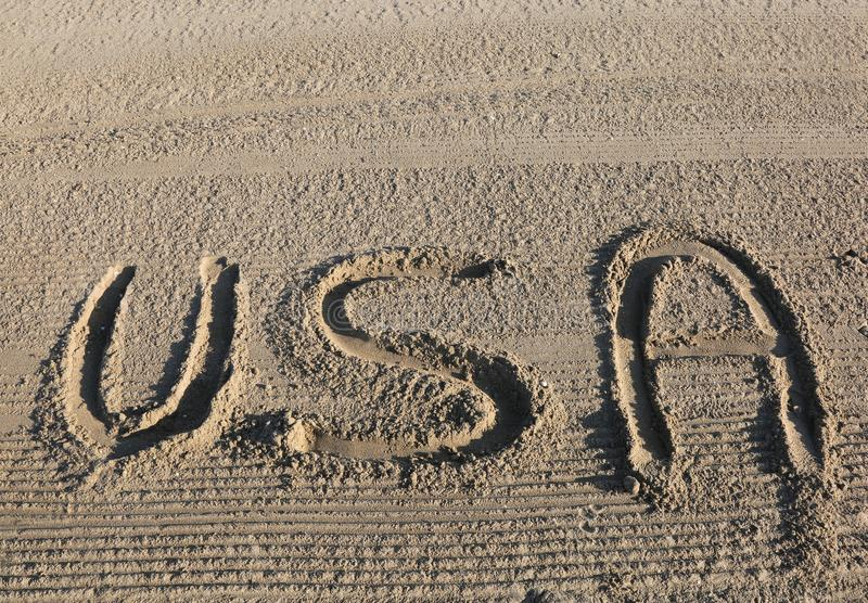 Big WORD USA United States of America on the sand of the beach. Big text WORD USA United States of America on the sand of the beach stock image