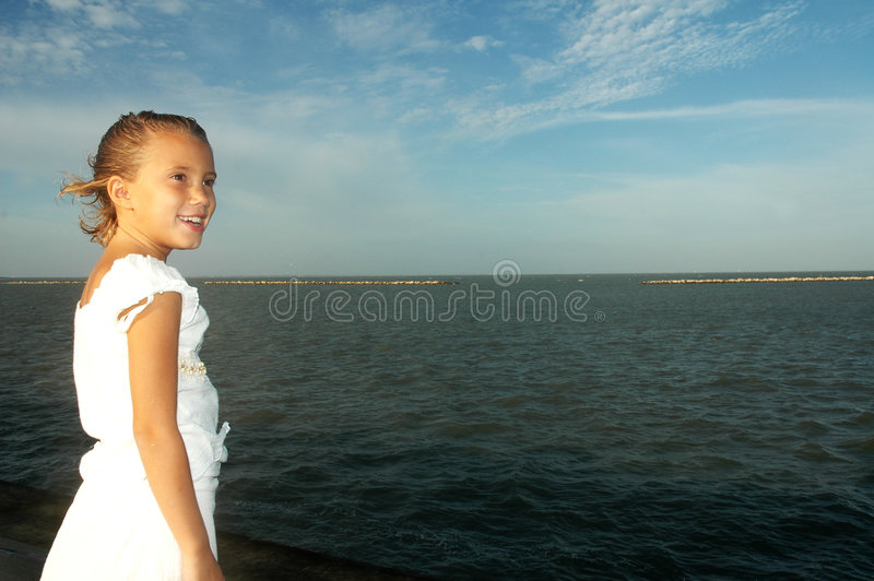 Big World. Little girl in a white dress stands facing the ocean off a stone wall. The wind blow threw her hair. Big smile on her face royalty free stock images