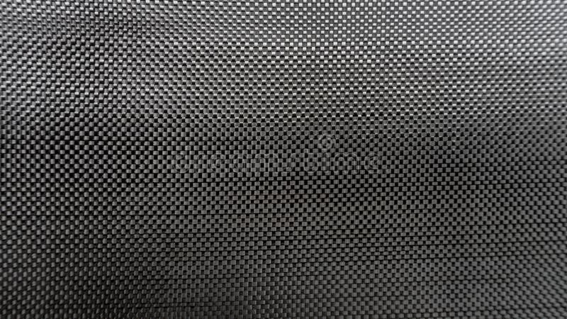 Plain weave woven Black carbon fiber composite material background close up view. Big woven Black carbon fiber composite material background close up view royalty free stock image