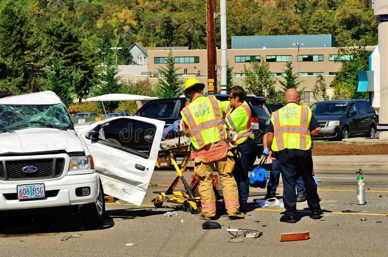 Big Wreck. Firefighters and paramedics extricate the victims of a two vehicle t-bone type accident at an intersection resulted in major jinjuries due to failure royalty free stock photo