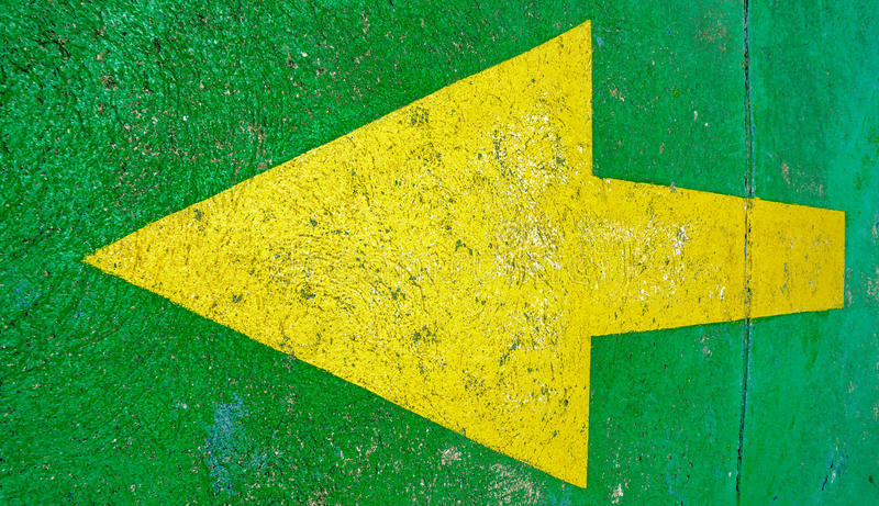 Big yellow arrow pointing to the left with green background stock image