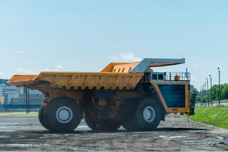 Career dump truck on a sunny day, tested. Big yellow Career heavy-load car, dump truck stock photography