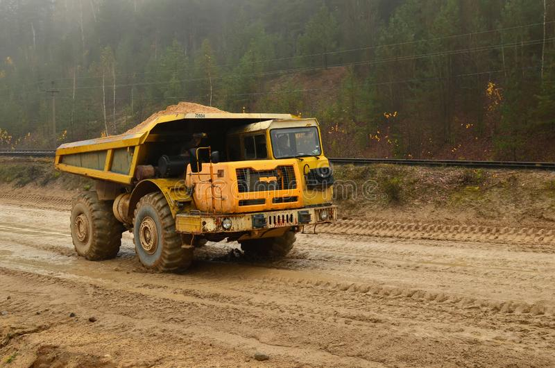 Big yellow diesel quarry dumper at work. Heavy mining truck transporting sand and clay stock photo