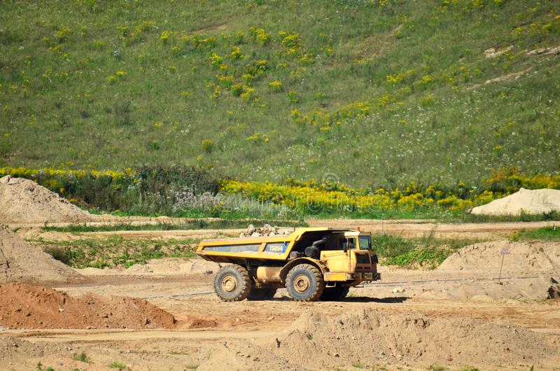 Big yellow dump truck transporting stone and gravel in an sand open-pit. Mining quarry for the production of crushed stone, sand and gravel for use in the royalty free stock photo