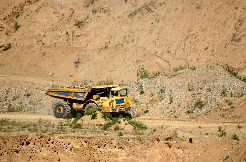 Big yellow dump truck transporting stone and gravel in an sand open-pit. Mining quarry for the production of crushed stone, sand and gravel for use in the stock image
