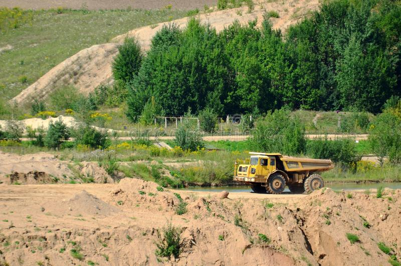 Big yellow dump truck transporting stone and gravel in an sand open-pit. Mining quarry for the production of crushed stone, sand and gravel for use in the royalty free stock images