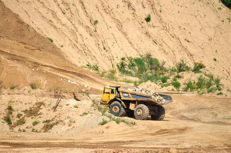 Big yellow dump truck transporting stone and gravel in an sand open-pit. Mining quarry for the production of crushed stone, sand and gravel for use in the stock photos