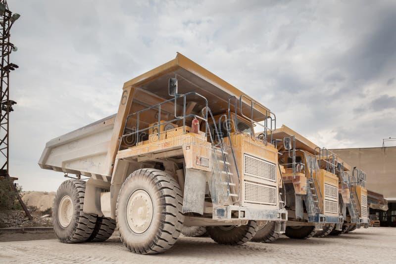 Big yellow dump trucks in the stone quarry. Mining trucks, mining machinery for transport stock photography
