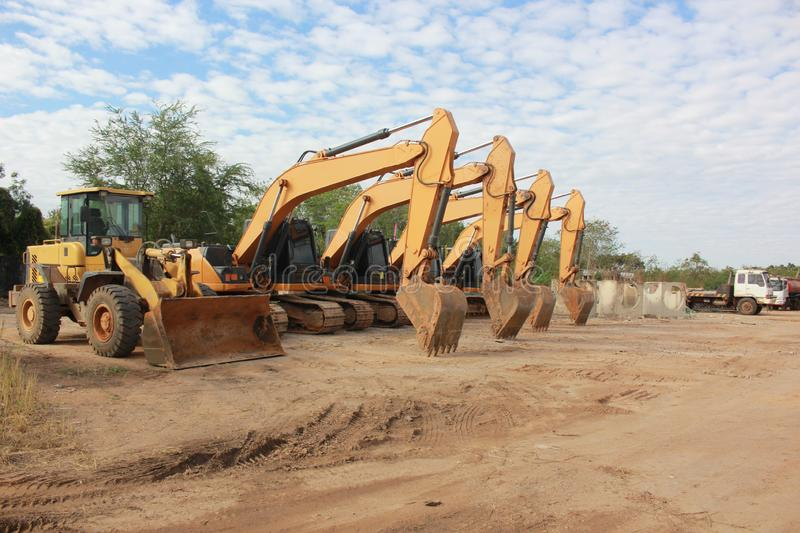 Big yellow excavator and other construction machinery in working space stock photos