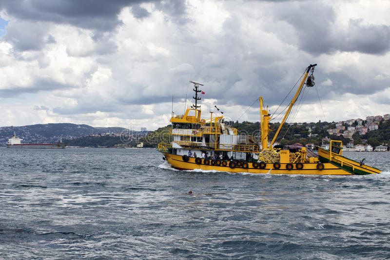 Big, yellow fishing boat and fishermen royalty free stock image