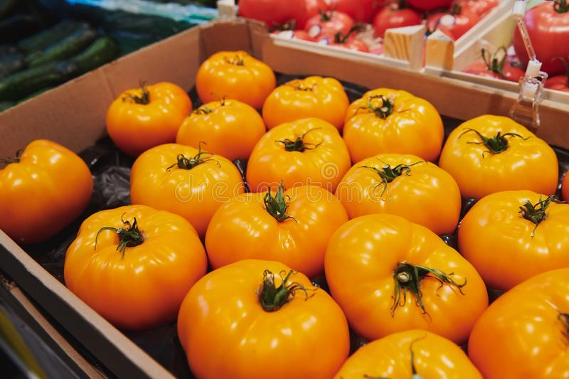 Big yellow heirloom tomatoes in the box at the market place. stock photography
