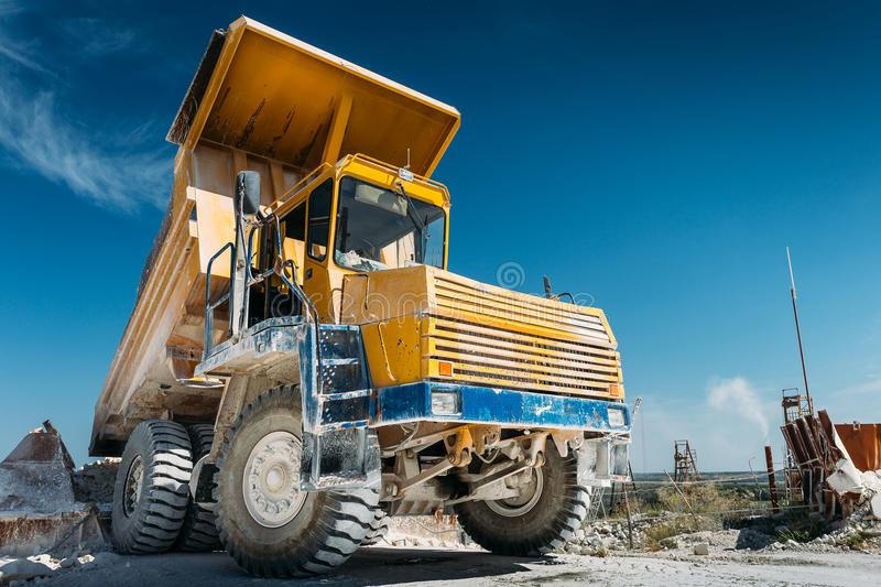 Big yellow mining truck vehicle, truck unloads mined ore or chalk or limestone. Mining industry concept royalty free stock image